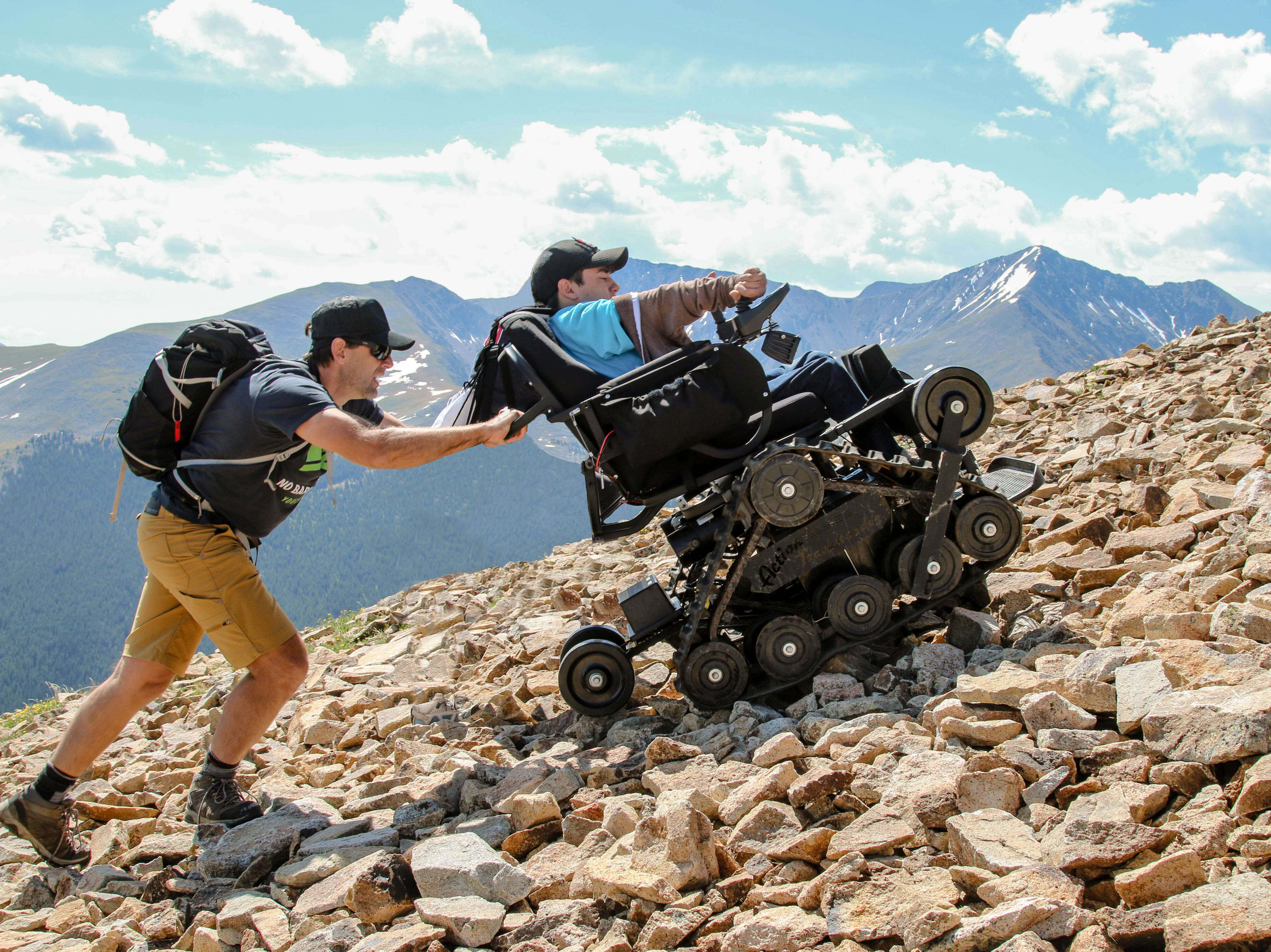 Two men hike up a rocky slope. One is using an electric wheelchair with tank-like treds, the other is helping to push the chair up the hill. There are mountains and a blue sky in the background.