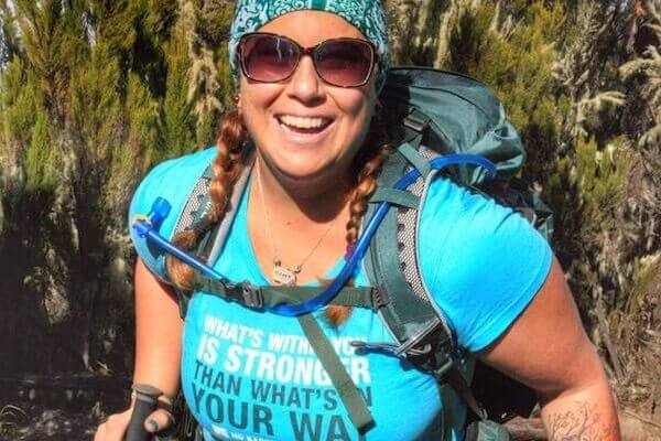 woman smiling and trekking while wearing no barriers shirt