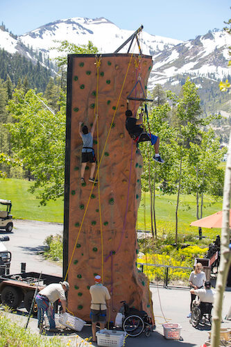 two men with disabilities climbing a rock wall and participating in physical activities for special needs students