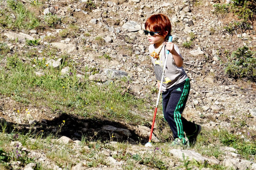 a small boy with no sight hiking and participating in physical activities for special needs students