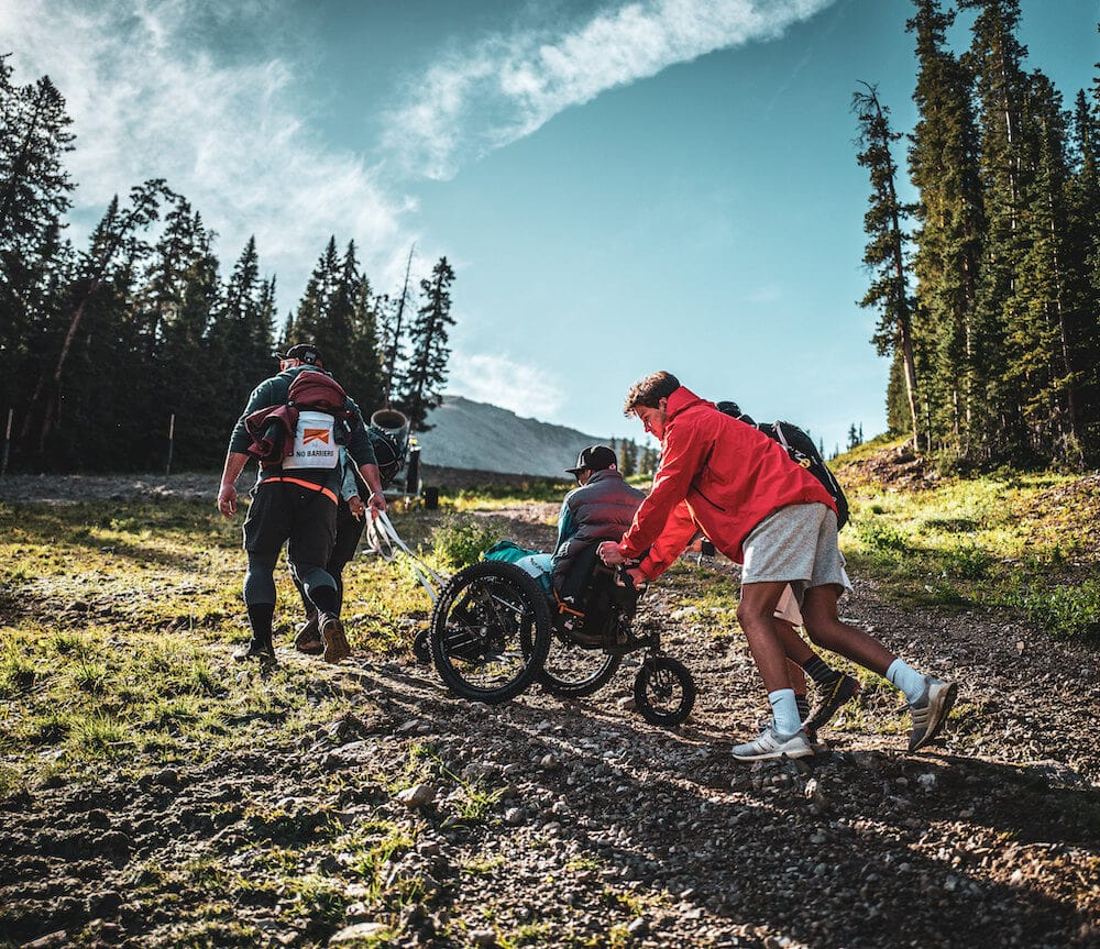 three men hiking and pushing up a wheelchair for physical activities for special needs students