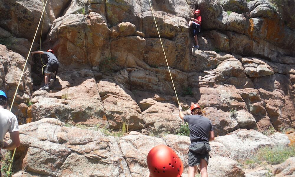 kids rock climbing in the outdoors at camp