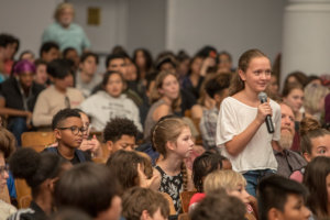 One youth speaking into a microphone in an auditorium full of children