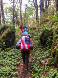 hiking with an American flag hung on backpack