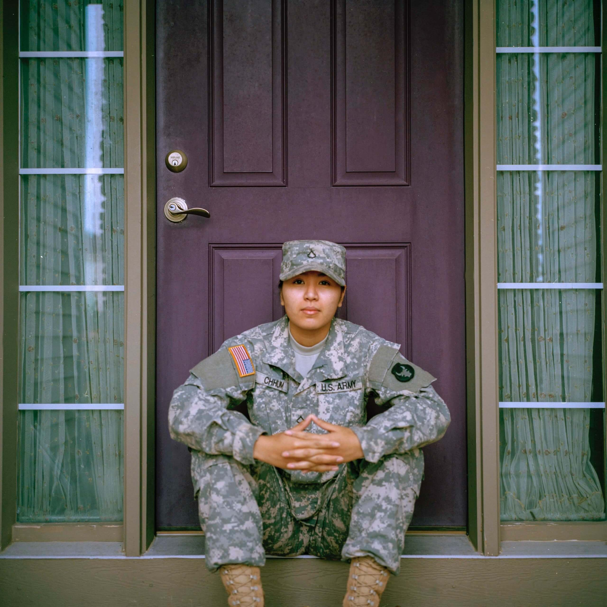 Woman in army uniform sitting in front of a door