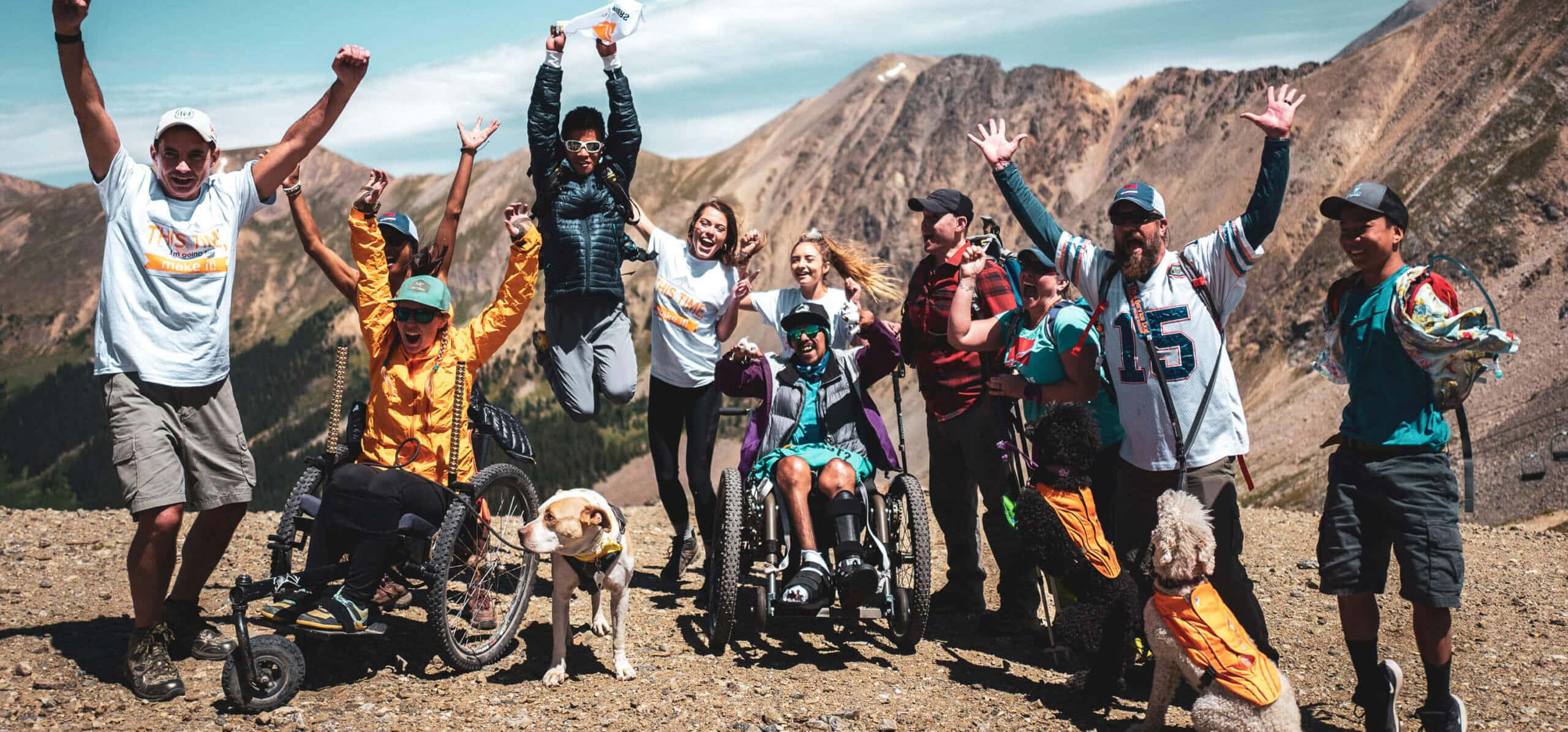 Group of mixed ability individuals jumping while at summit of a mountain