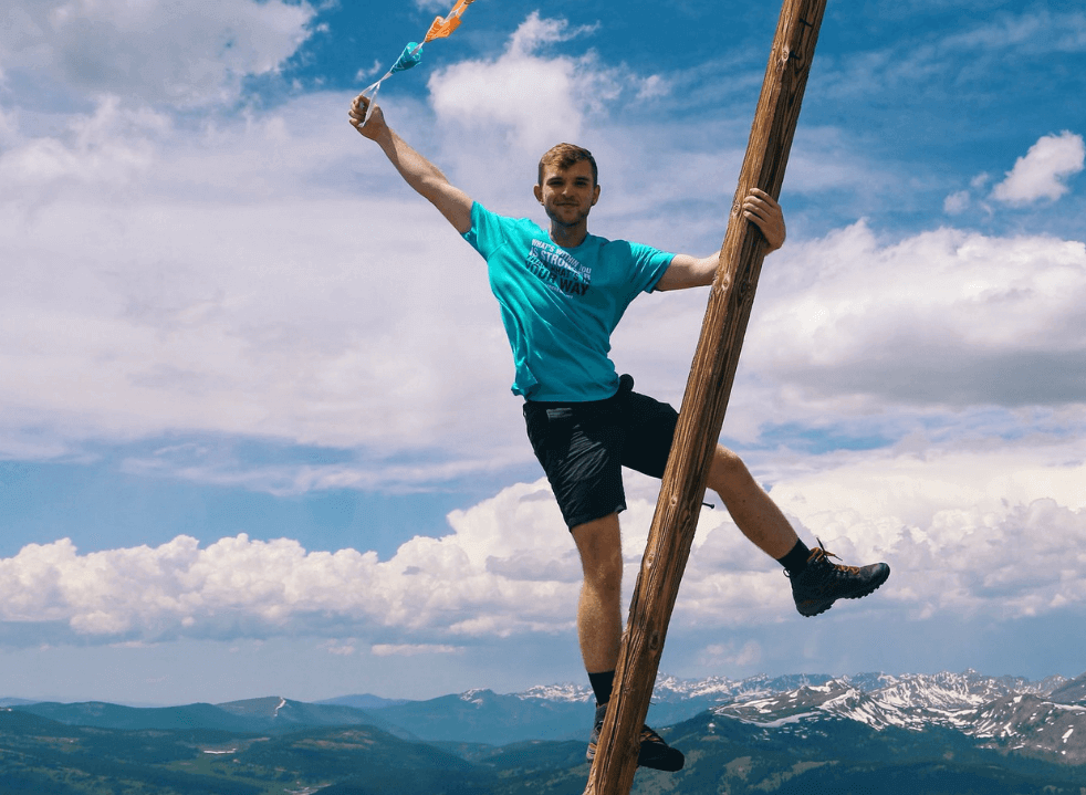 Picture of kid on a pole with mountain backdrop and flags in hand
