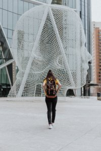 Girl with a backpack in front of a sculpture.