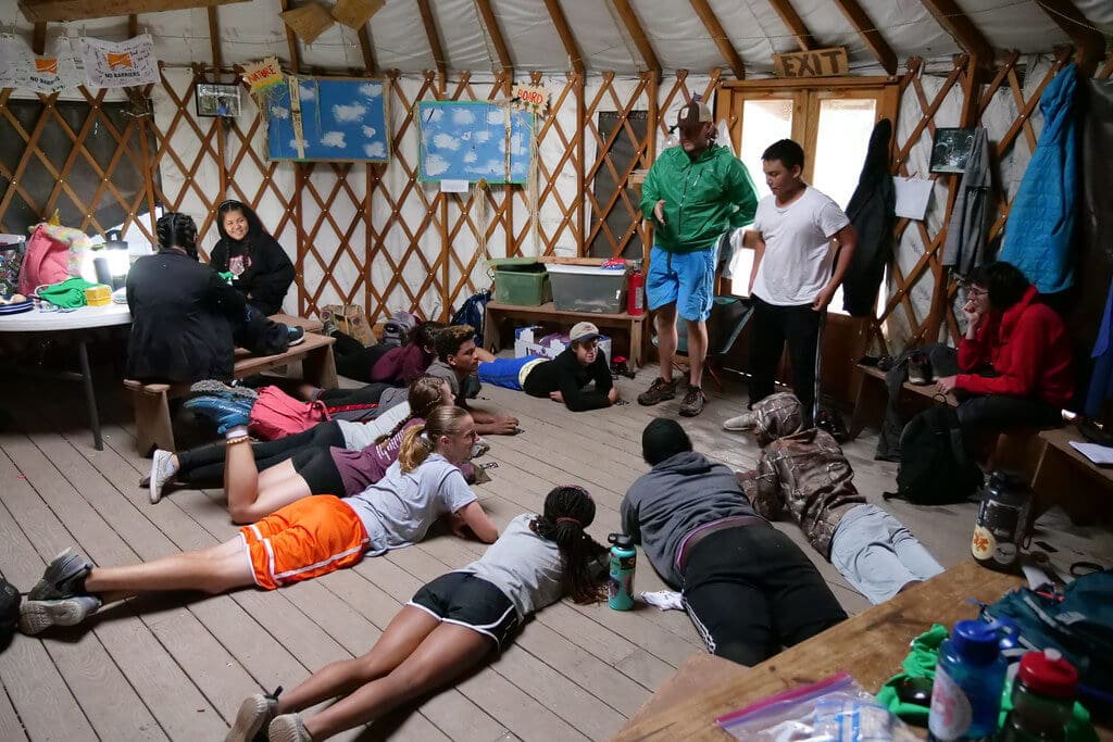 Youth gathered in a group in a yurt.