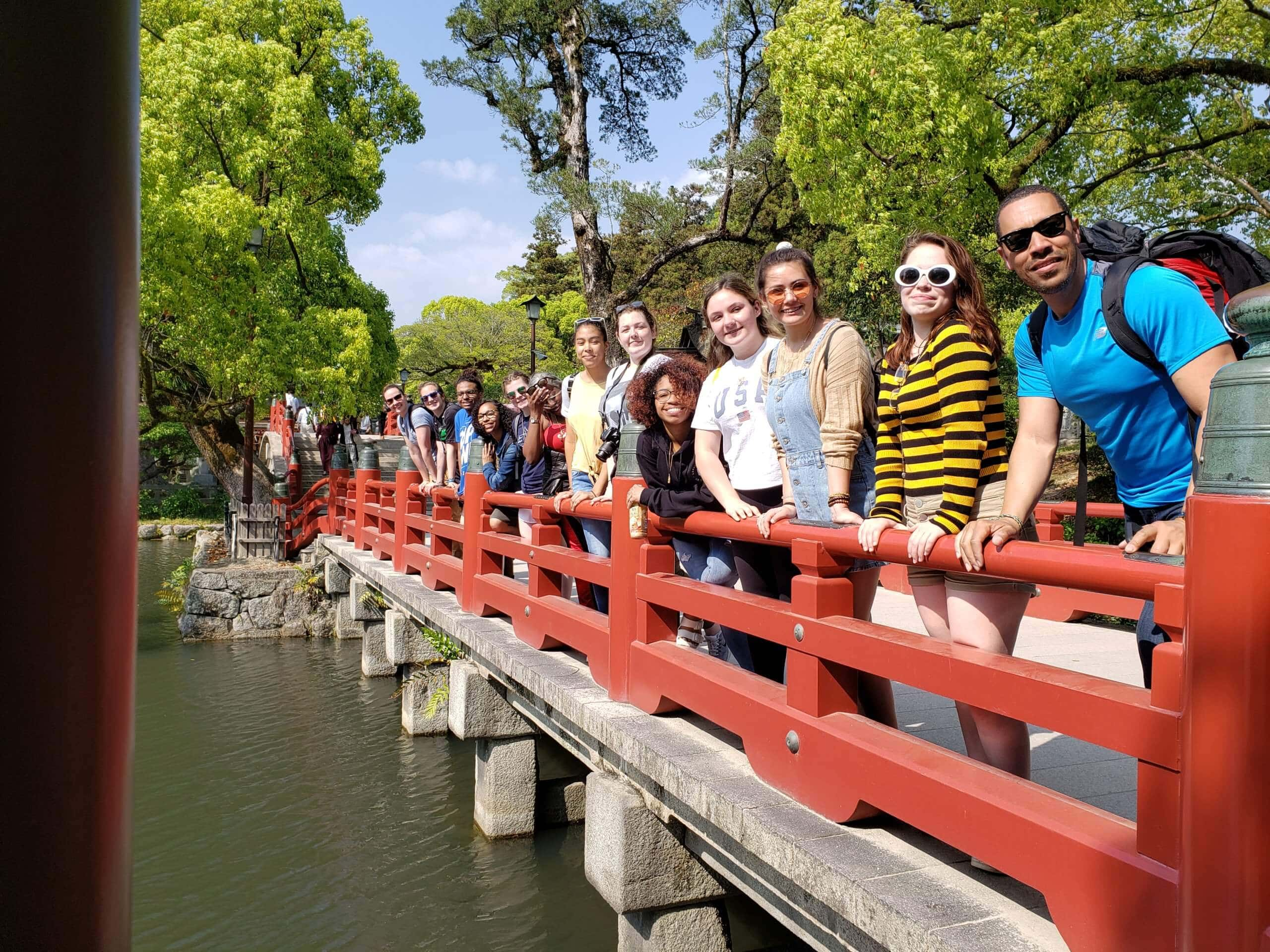 Students smiling on bridge in Japan